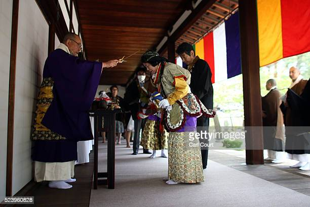 A woman is blessed by a priest before dressing as one of 25 Buddhist saints and marching at the Chionji temple on April 23 2016 in Kyoto Japan This...