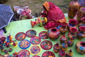 A woman is busy colouring earthenware Pottery is quite famous in West Bengal The smallscale industry of pottery is carried on mainly in the three...