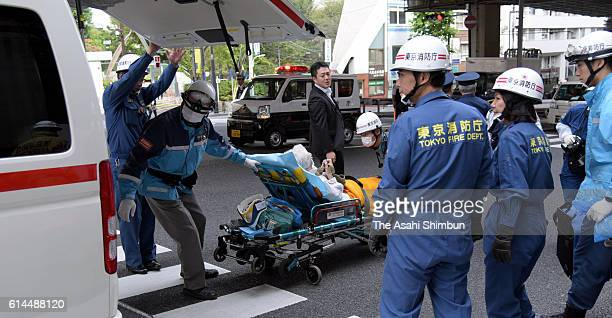 A woman is carried from the scene of an accident in which Kazuhiko Iimura was killed by a steel pipe that fell from scaffolding on October 14 2016 in...