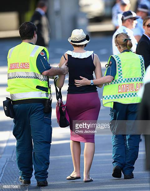 A woman is carried lead off by ambulance staff after feeling faint in the heat ahead of a royal walkabout on on the South Bank on April 19 2014 in...