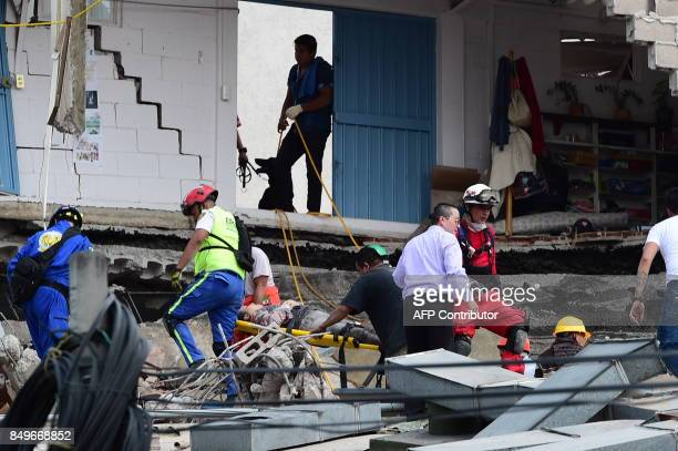 A woman is carried on a stretcher after being pulled out of the debris of a collapsed building following a quake in Mexico City on September 19 2017...