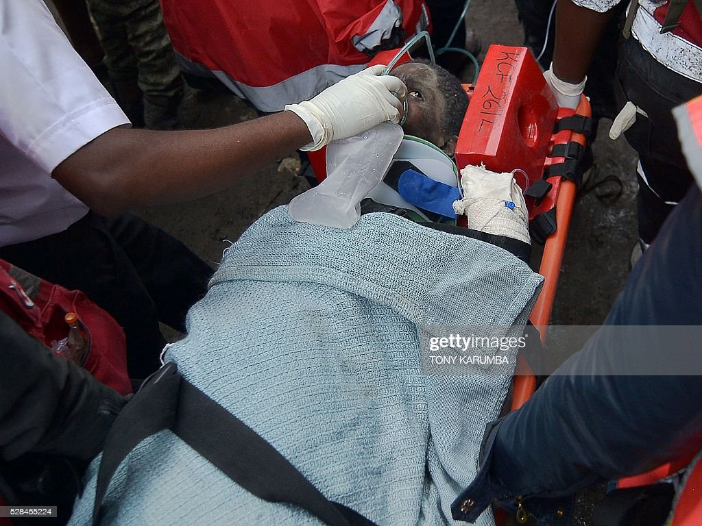 A woman is carried on a stretcher by medical personnel after she was rescued alive on May 5, 2016 after being trapped in the rubble of a residential house that collapsed during torrential rain in Kenyan capital, Nairobi's low-income suburb of Huruma. The woman was pulled out hours after being located on May 5, 2016 morning by rescuers who gave her oxygen while they continued efforts to extract her from the ruins of the six-storey building / AFP / TONY