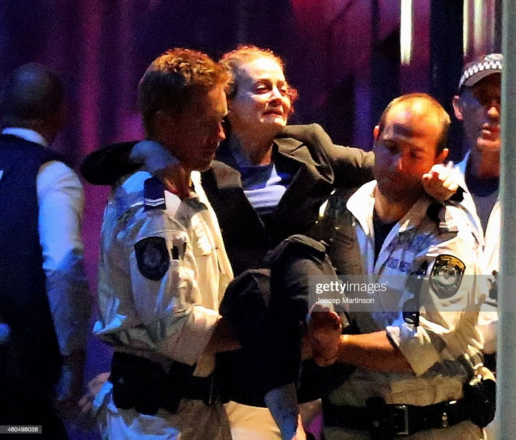 A woman is carried out by police from the Lindt Cafe Martin Place following a hostage standoff on December 16 2014 in Sydney Australia Police stormed...