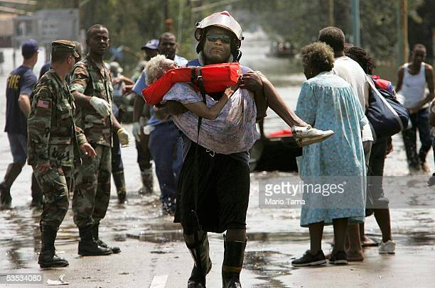A woman is carried out of flood waters after being trapped in her home in Orleans parish during the aftermath of Hurricane Katrina August 30 2005 in...