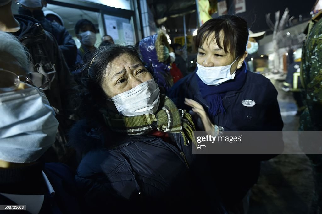 A woman (C) is comforted as rescue personnel continue work at the site of a collapsed building in the southern Taiwanese city of Tainan on February 6, 2016 following a strong 6.4-magnitude earthquake. A powerful earthquake in Taiwan felled a 16-storey apartment complex full of families who had gathered for Lunar New Year celebrations in the early hours of February 6, with at least seven dead and more than 30 feared trapped. AFP PHOTO / Sam Yeh / AFP / SAM YEH