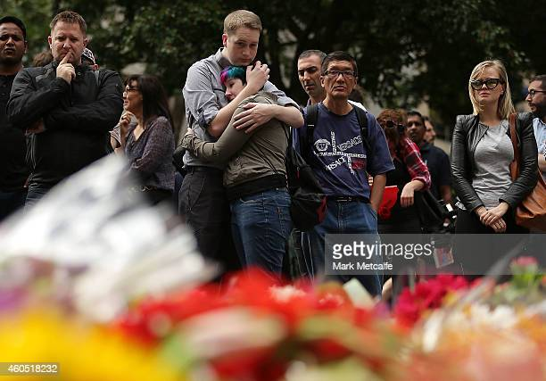 A woman is comforted as she pays her respect at Martin Place on December 16 2014 in Sydney Australia The siege in Sydney's Lindt Cafe in Martin Place...