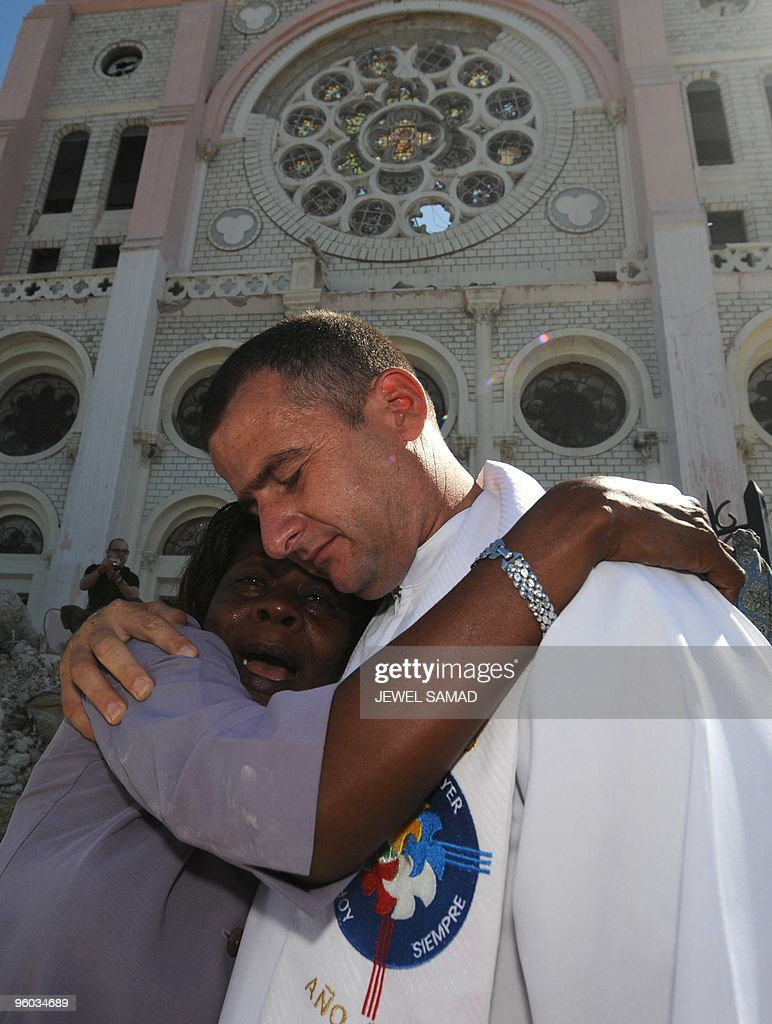 A woman is comforted by a priest after the funeral of Haitian Archbishopo Joseph Serge Miot killed in last week's devastating earthquake outside Notre Dame d'Assumption Cathedral in Port-au-Prince on January 23, 2010. More than 110,000 people have been confirmed as killed in Haiti's devastating earthquake, the Interior Ministry said, making it the deadliest on record in the Americas. AFP PHOTO / JEWEL SAMAD