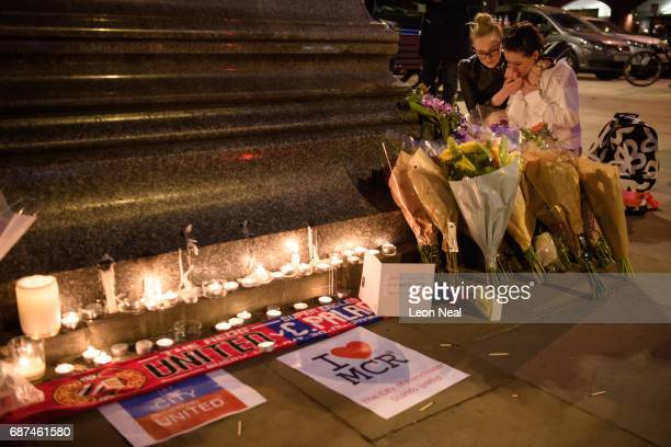 A woman is consoled as she looks at the floral tributes following an evening vigil outside the Town Hall on May 23 2017 in Manchester England An...