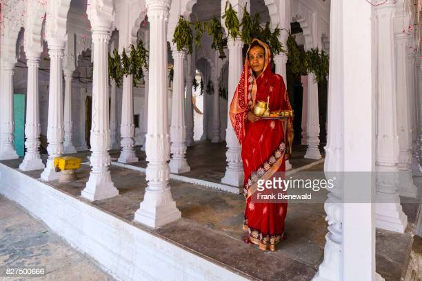 A woman is doing Pooja offerings to the Gods in a small hindu temple with white pillars in the suburb Godowlia