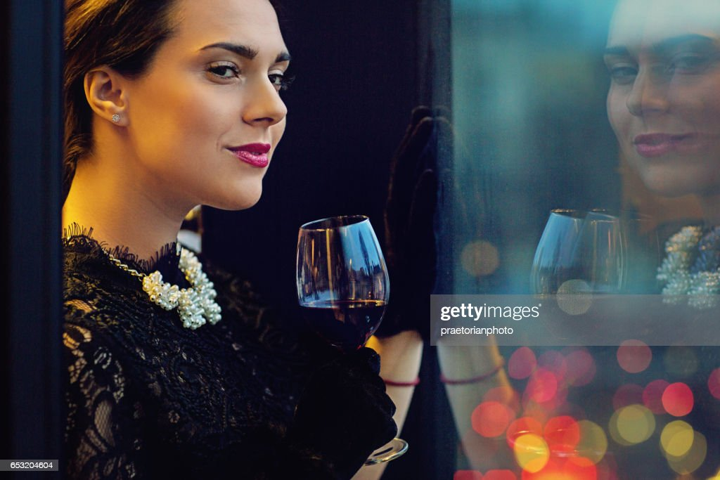 Woman is drinking wine and looking trough the window : Stock Photo