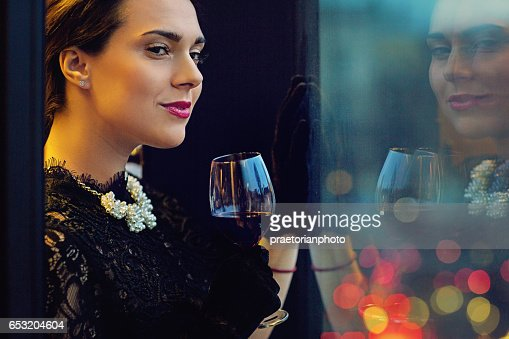 Woman is drinking wine and looking trough the window : Stock-Foto