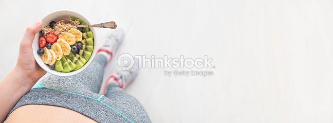 Woman is eating a healthy oatmeal after a workout. : Stock Photo