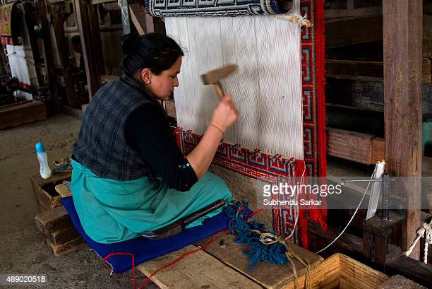 A woman is engaged in weaving carpet at Tibetan Refugee Self Help Centre The Tibetan Refugee Self Help Centre of Darjeeling was started on October 2...
