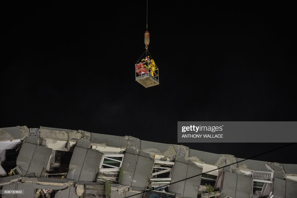 A woman is extracted by a crane from the rubble of a collapsed building in the southern Taiwanese city of Tainan following a strong 6.4-magnitude earthquake that struck early on February 6, 2016. A powerful earthquake in Taiwan felled a 16-storey apartment complex full of families who had gathered for Lunar New Year celebrations February 6, with at least eleven dead and more than 30 feared trapped. AFP PHOTO / ANTHONY WALLACE / AFP / ANTHONY WALLACE