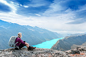 Young tourist woman is feeling free and sitting on the top of the mounting and looking at a beautiful landscape