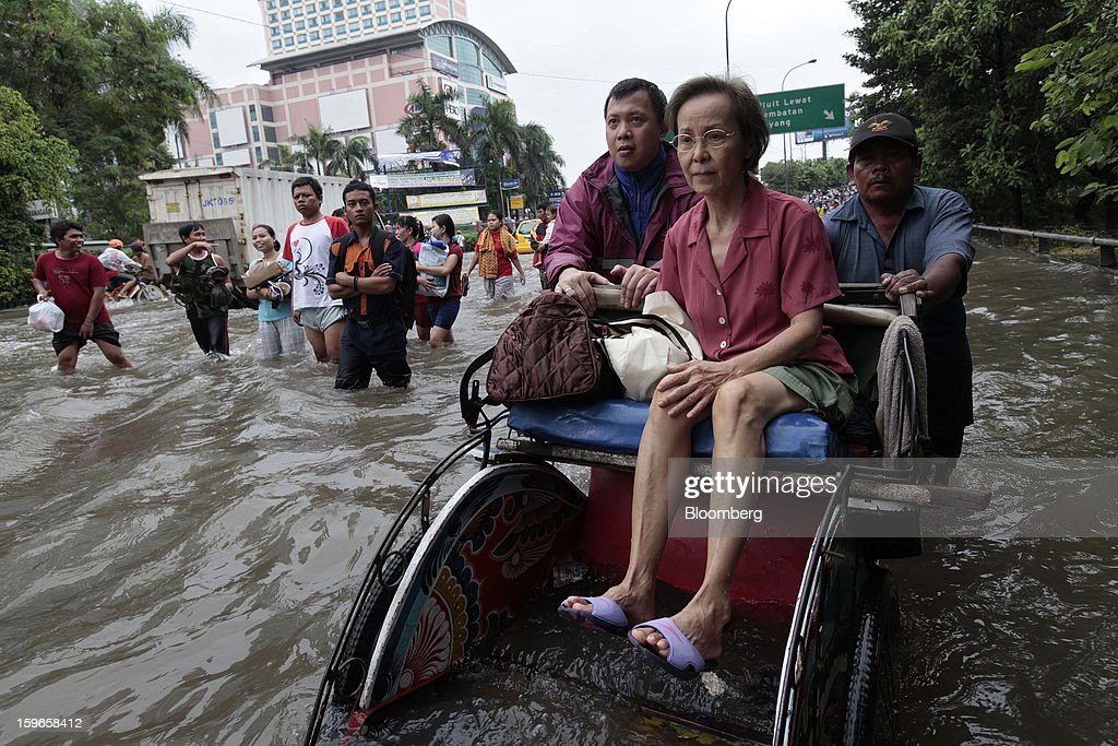 A woman is ferried through floodwaters on a rickshaw in Jakarta, Indonesia, on Friday, Jan. 18, 2013. Indonesia declared a state of emergency in Jakarta as flooding brought traffic to a standstill in the city of 9.6 million people and swamped the offices of President Susilo Bambang Yudhoyono. Photograph by: Dimas Ardian/Bloomberg via Getty Images
