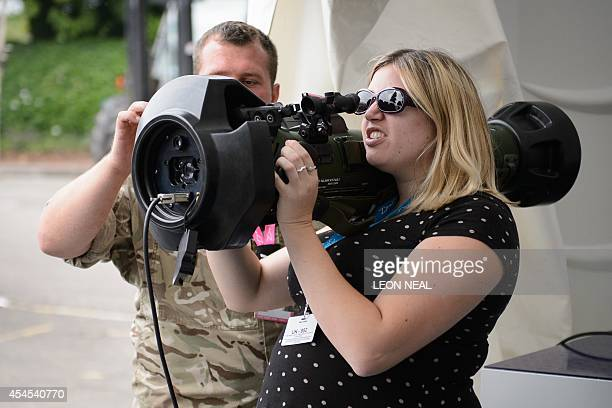A woman is given a demonstration of a piece of Bofors Dynamics military hardware AT4CS on one of the exhibition stands at Celtic Manor Resort on...