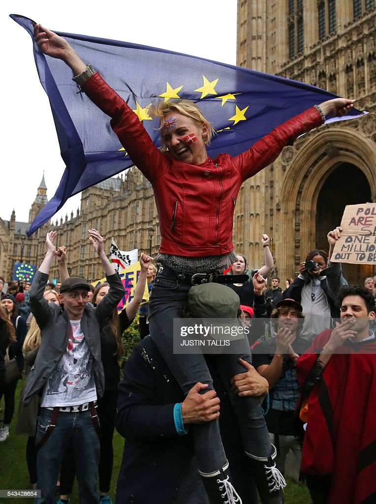 A woman is held aloft as she dances with a European flag as demonstrators march onto College Green outside The Houses of Parliament at an anti-Brexit protest in central London on June 28, 2016. EU leaders attempted to rescue the European project and Prime Minister David Cameron sought to calm fears over Britain's vote to leave the bloc as ratings agencies downgraded the country. Britain has been pitched into uncertainty by the June 23 referendum result, with Cameron announcing his resignation, the economy facing a string of shocks and Scotland making a fresh threat to break away. / AFP / JUSTIN