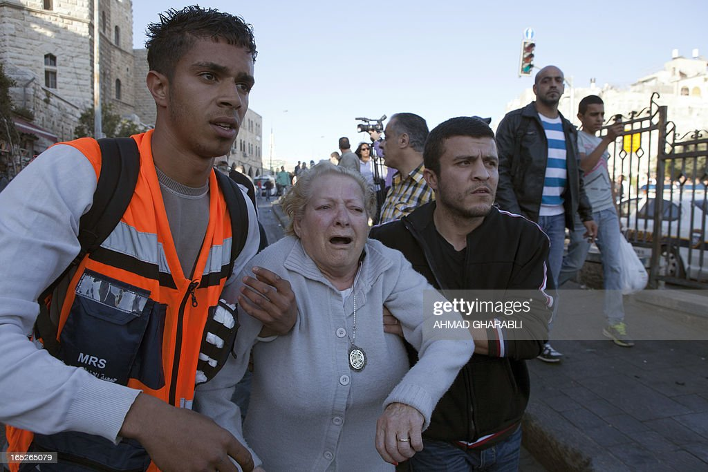 A woman is helped away as Israeli security arrest protesters during clashes following the death of a Palestinian prisoner being held in an Israeli jail, on April 2, 2013, at the entrance of Jerusalem's Old City next to the Damascus Gate. The Palestinian leadership blamed Israel for the death of Maisara Abu Hamdiyeh, a long-term prisoner with cancer, hiking tensions over a tinderbox issue closely followed on the Palestinian street. AFP PHOTO/AHMAD GHARABLI
