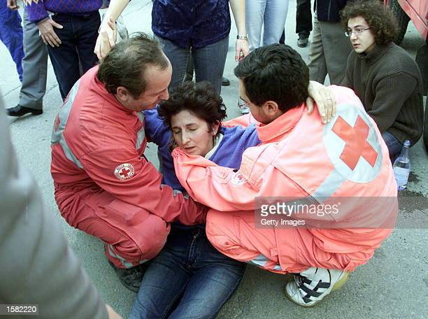 A woman is helped by emergency workers after she collapsed as another strong tremor measuring 53 on the Richter scale struck November 1 2002 San...