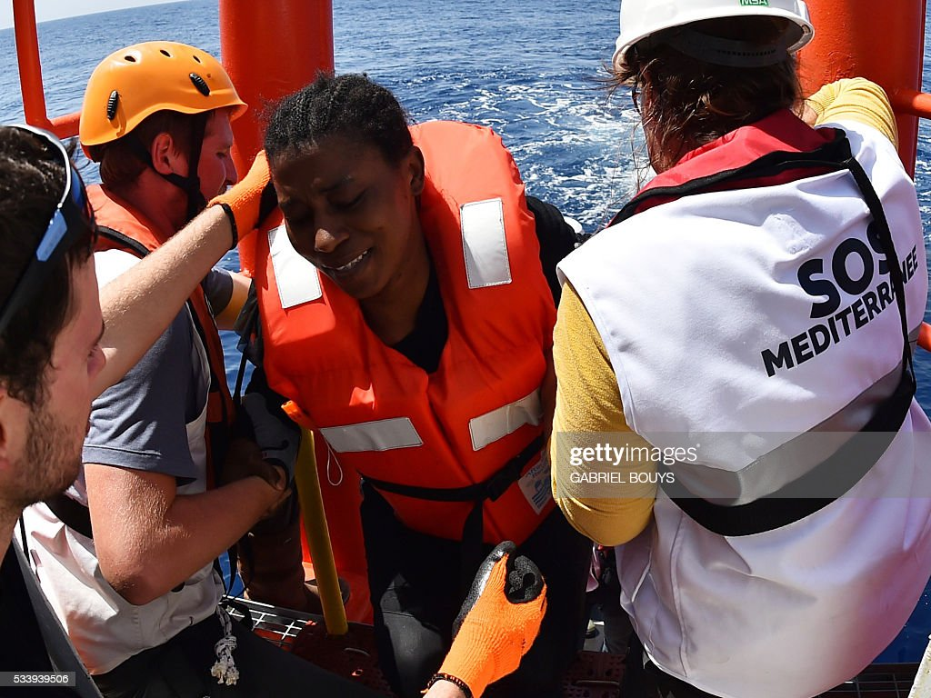A woman is helped by rescuers during a rescue operation at sea of migrants and refugees with the Aquarius, a former North Atlantic fisheries protection ship now used by humanitarians SOS Mediterranee and Medecins Sans Frontieres (Doctors without Borders), on May 24, 2016 in the Mediterranean sea in front of the Libyan coast. / AFP / GABRIEL