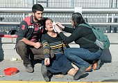 A woman is helped following an explosion at the main train station in Turkey's capital Ankara on October 10 2015 At least 20 people were killed in...