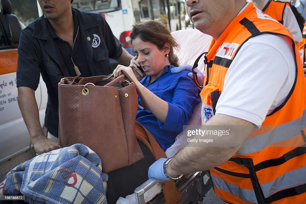 A woman is helped from the scene by emergency services after an explosion on a bus with passengers onboard on November 21, 2012 in central Tel Aviv, Israel. At least ten people have been injured in a blast on a bus near military headquarters in what is being described as terrorist attack which threatens to derail ongoing cease-fire negotiations between Israeli and Palestinian authorities.