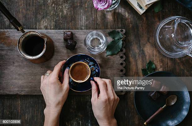 A woman is holding a cup of Turkish coffee with foam on top (with both hands) that is served with water and chocolate. Photographed from the top.