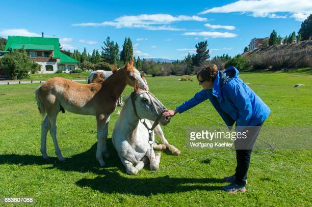 Woman is interacting with the horses at the Estancia Hotel Kau Yatun in El Calafate Argentina