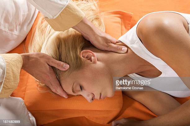 A woman is laying down while hands massage her head
