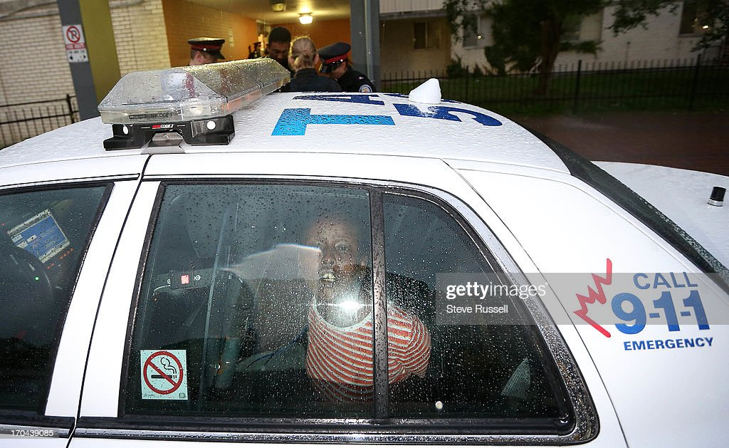 A woman is lead out by police into a cruiser as police raid buildings at 320, 330 and 340 Dixon Road, concentrating on 320. Police in tactical gear were working with the Guns and Gangs unit. Toronto Police launched a massive predawn raid on June 13, 2013, targeting guns and drugs. The focus is on the Toronto neighbourhood thats ground zero for the Mayor Rob Ford crack video scandal.
