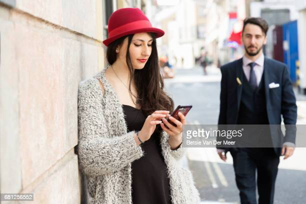 Woman is looking at her phone while waiting, boyfriend is walking towards her.