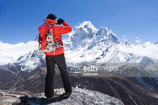 Woman is looking through binoculars in Mount Everest National Park : Stock Photo