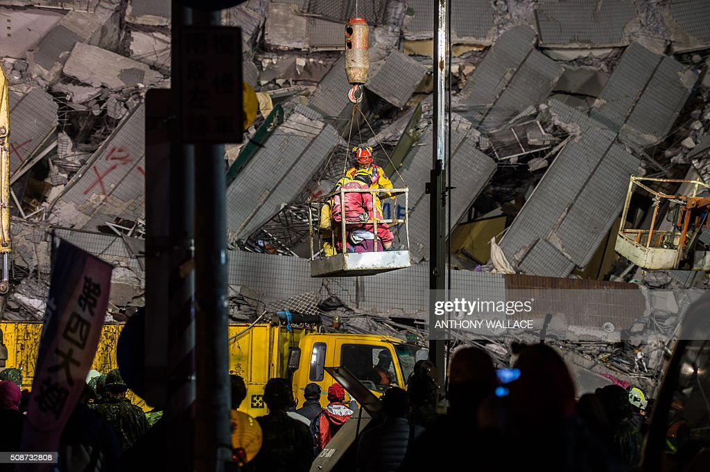 A woman is lowered to the ground after being extracted by a crane from the rubble of a collapsed building in the southern Taiwanese city of Tainan following a strong 6.4-magnitude earthquake that struck early on February 6, 2016. A powerful earthquake in Taiwan felled a 16-storey apartment complex full of families who had gathered for Lunar New Year celebrations February 6, with at least eleven dead and more than 30 feared trapped. AFP PHOTO / ANTHONY WALLACE / AFP / ANTHONY WALLACE