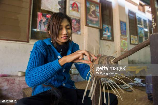 A woman is making a small basket out of bamboo at a lacquerware workshop in Bagan Myanmar
