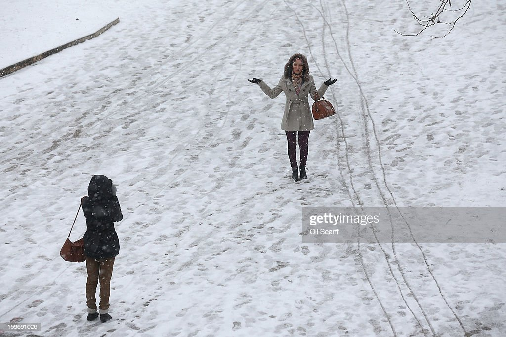 A woman is photographed by her friend on a snow-covered South Bank of the river Thames on January 18, 2013 in London, England. Widespread snowfall is affecting most of the UK with school closures and transport disruption. The Met Office has issued a red weather warning for parts of Wales, advising against all non-essential travel as up to 30cm of snow is expected to fall in some areas today..