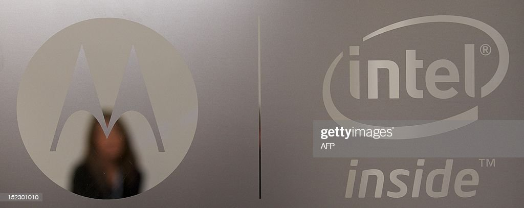 A woman is photographed through a door with Motorola and Intel branding logos during the press launch of the new Motorola RAZRi smartphone with an Intel processor in London on September 18, 2012. Motorola Mobility presented their new smartphone, developed with an Intel processor powering its Android operating system, which will be launched in October in Europe and Latin America with the hope that it will compete with the Apple iPhone.