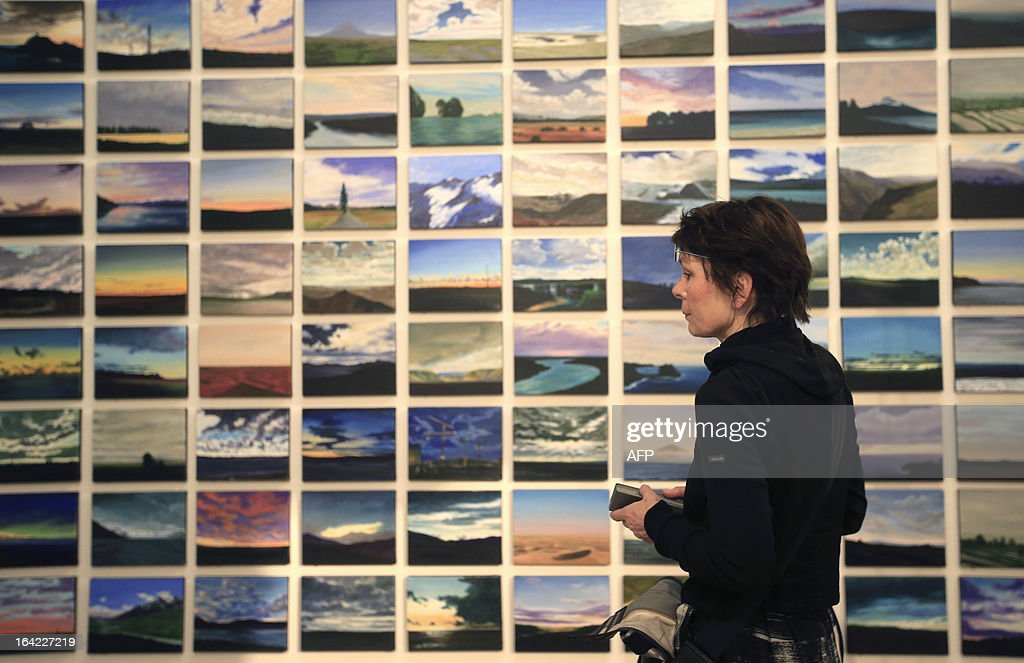 A woman is pictured in front of an artwork by French artist Olivier Masmonteil, titled 'Quelle que soit la minute du jour', as part of the 'Clouds' (Wolken) exhibition at the Leopold Museum in Vienna, on March 21, 2013. The exhibition will run until July 1, 2013.