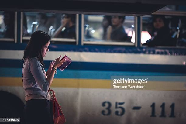A woman is playing the internet on her smart phone at a bus stop