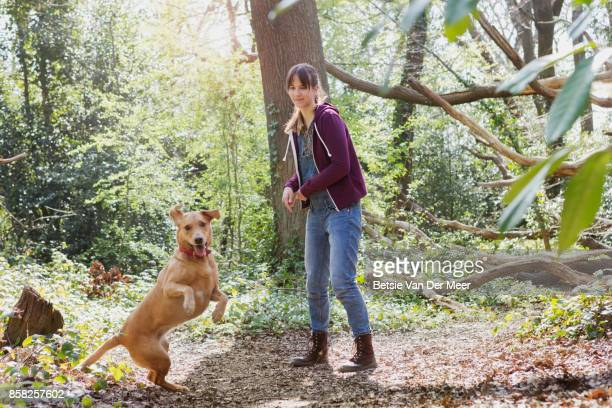 Woman is playing with her dog in woods.