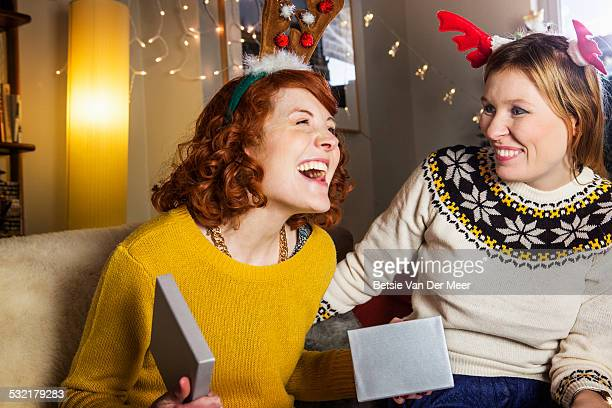 Woman is pleased when opening Christmas present.