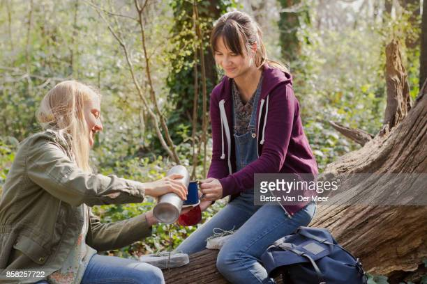 Woman is pouring drink into friends cup, both sitting on treetrunk in forest.