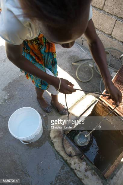 PortauPrince Haiti December 09 2012 A woman is pulling up a plastic bucket on a string to get water from a hole in the refugee camp Parc Colofe in...