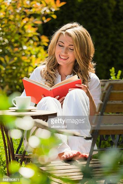 woman is reading a book in the garden