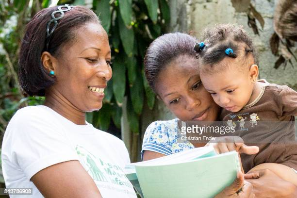 Santa Domingo Dominican Republic November 30 2012 A woman is reading a magazine with her daughter in her arms in the poor neighbourhood 'Los...
