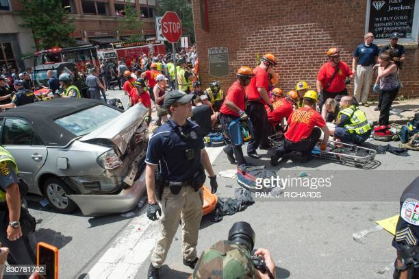 TOPSHOT A woman is received firstaid after a car accident ran into a crowd of protesters in Charlottesville VA on August 12 2017 A picturesque...