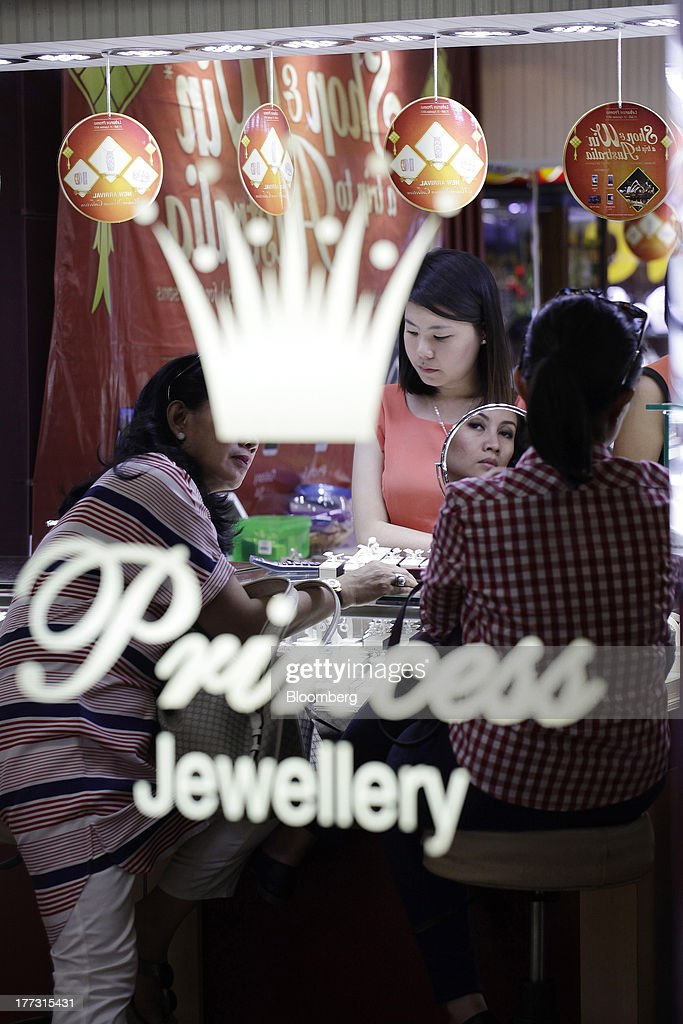 A woman is reflected in a mirror as she tries on jewelry at a jewelry store in Jakarta, Indonesia, on Thursday, Aug. 22, 2013. Gold jewelry demand in Indonesia is set to expand to a four-year high as consumers in Southeast Asia's biggest buyer join India to China in increasing purchases as prices slump and the middle class expands. Photographer: Dimas Ardian/Bloomberg via Getty Images