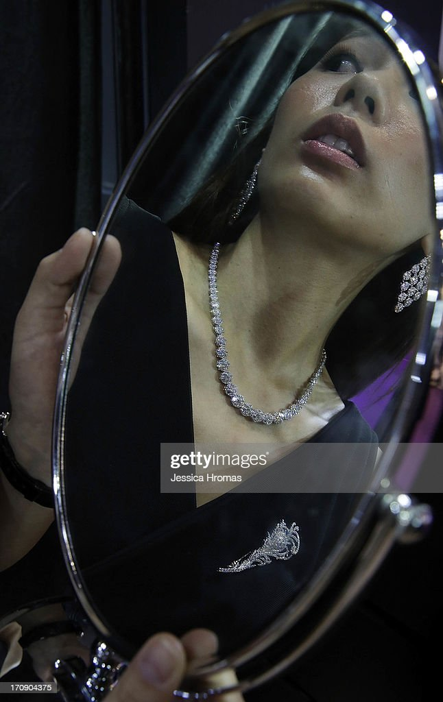 A woman is reflected in a mirror she is holding, wearing jewellery by Hong Kong Jeweller 'Golden Master Jewellery', a diamond necklace with a total weight of 23 karts of diamonds, valued at USD$35,000, diamond earrings with 12 karts of diamonds valued at USD$13,000 and a diamond broach with a total of 5 karts of diamonds, valued at USD$6,000, at the Hong Kong Jewellery and Gem Fair on June 20, 2013 in Hong Kong, Hong Kong. The June Hong Kong Jewellery & Gem Fair runs from June 20 - 23.