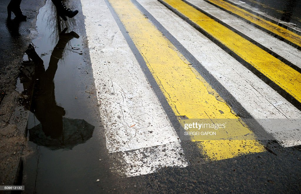 A woman is reflected in a puddle as she crosses a road in Minsk, during warm winter weather with temperatures at three degree Celsius on February 11, 2016. AFP PHOTO / SERGEI GAPON / AFP / SERGEI GAPON