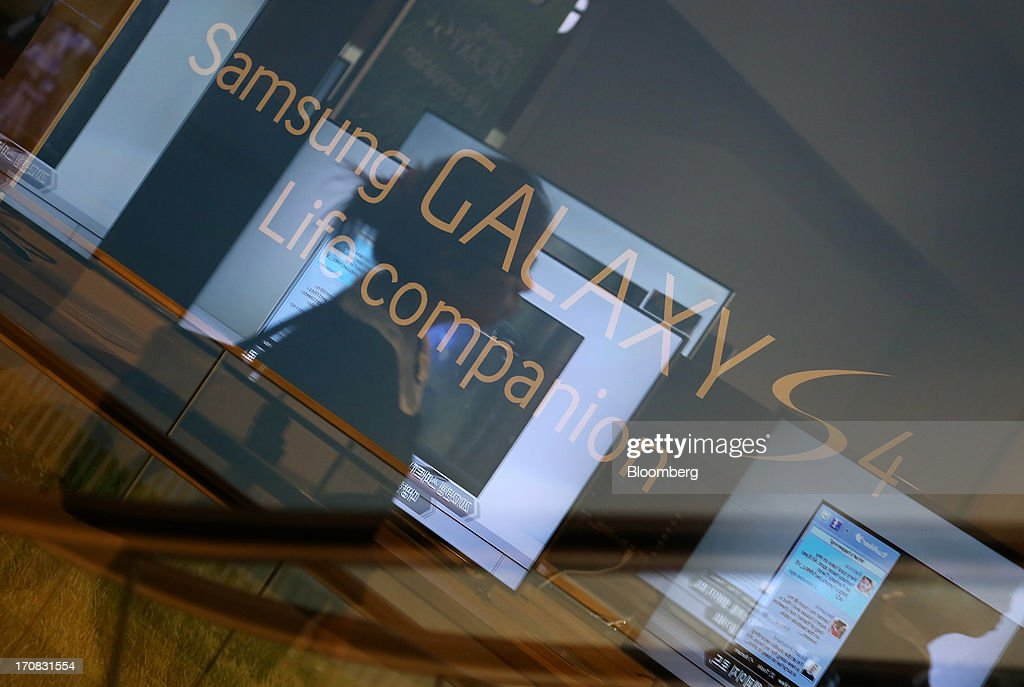 A woman is reflected in a window as an advertisement for Samsung Electronics Co. Galaxy S4 smartphone is displayed in the background at the Samsung d'light store in Seoul, South Korea, on Tuesday, June 18, 2013. Facebook Inc. Chief Executive Officer Mark Zuckerberg, seeking to boost advertising sales from mobile devices, discussed potential partnerships with Samsung Electronics Co., according to the head of the South Korean companys handset division. Photographer: SeongJoon Cho/Bloomberg via Getty Images